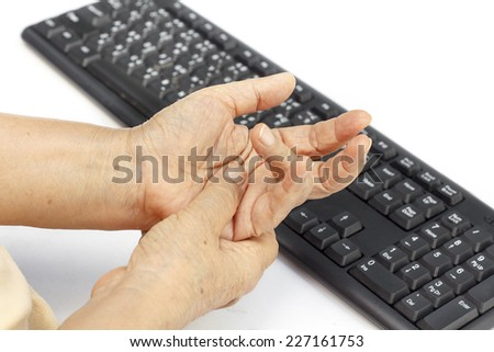 Senior woman painful finger due to prolonged use of keyboard and mouse. - stock photo