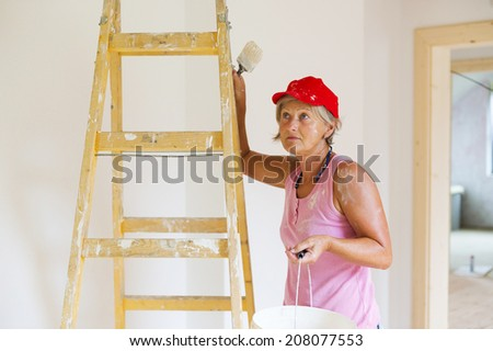 Senior woman painting wall in new house. She is using ladder. - stock photo