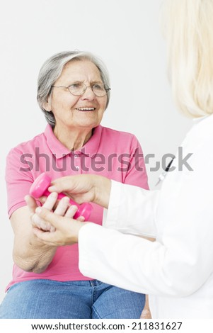 Senior woman  patient  lifts dumbbells with a  physical therapist.  - stock photo