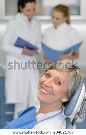 Senior woman patient with dentist team at dental surgery smiling - stock photo