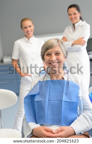 Senior woman patient with professional dentist team at dental surgery - stock photo