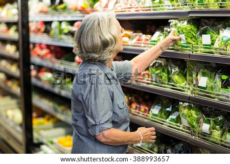 Senior woman picking out some vegetables in supermarket - stock photo