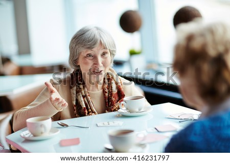 Senior woman playing cards with her friend - stock photo