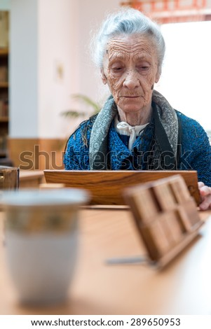 Senior woman playing rummy - stock photo