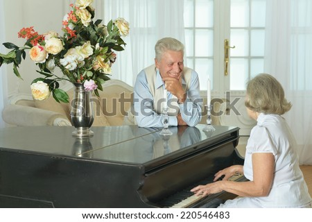 Senior woman playing the piano at home with her husband - stock photo
