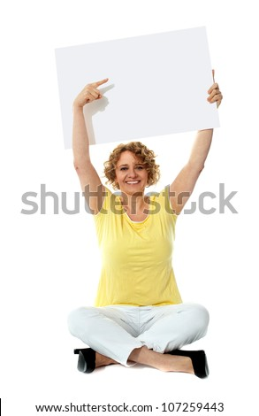 Senior woman pointing at blank ad board over her head - stock photo
