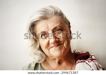 Senior woman portrait on grey background - stock photo