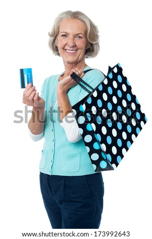 Senior woman posing with shopping bags and credit card - stock photo