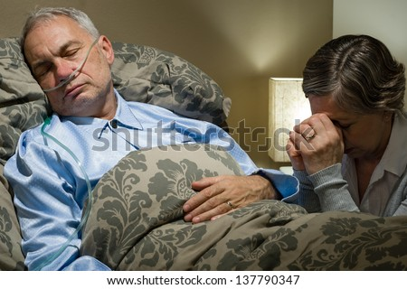 Senior woman praying for her sick husband lying in bed - stock photo