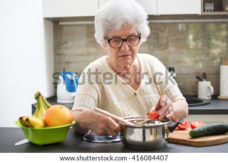 Senior woman preparing a meal with vegetables in the kitchen. - stock photo