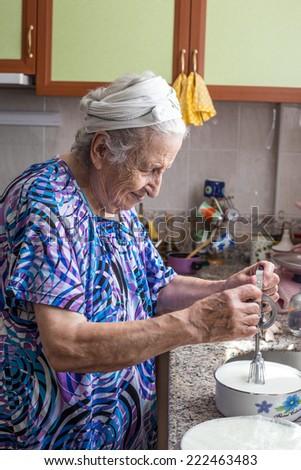 senior woman preparing food  in kitchen - stock photo