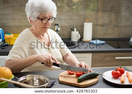 Senior woman preparing healthy food from fresh vegetables in kitchen. - stock photo