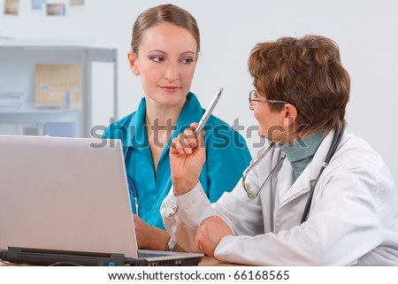 Senior woman professor explain to a young female medical student - stock photo