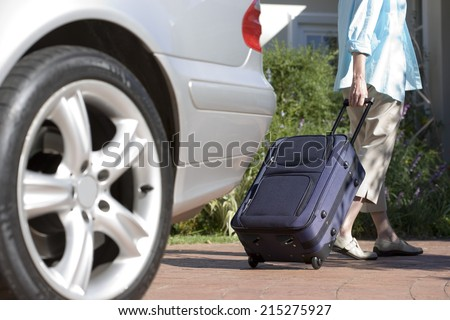 Senior woman pulling suitcase on wheels from parked car boot on driveway, rear view (surface level) - stock photo
