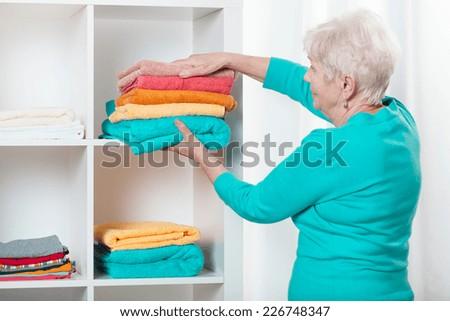 Senior woman putting towels to the shelf - stock photo