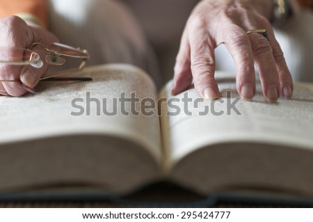Senior woman reading a book and in her hand she holds a pair of eyeglasses. - stock photo