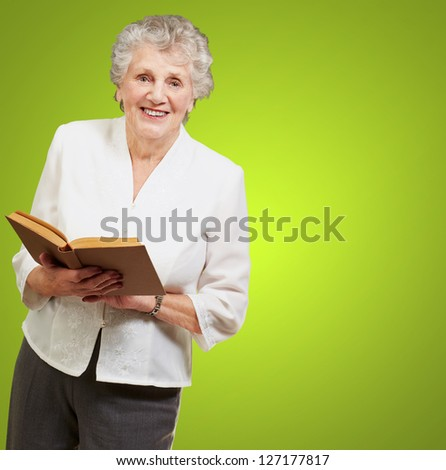 Senior woman reading a book isolated on green background - stock photo