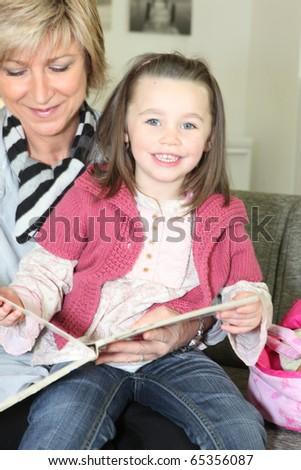 Senior woman reading a book to a little girl - stock photo