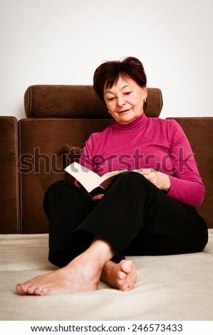 Senior woman reading book - stock photo