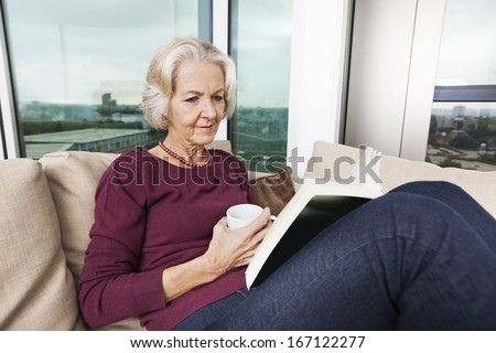 Senior woman reading book on sofa at home - stock photo