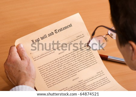 Senior woman reading Last Will and Testament sitting on desk - stock photo