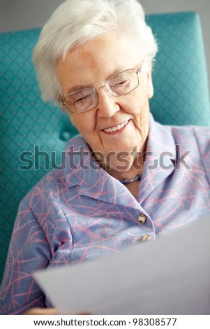 Senior Woman Relaxing In Chair Reading Letter - stock photo