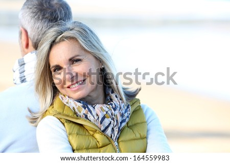 Senior woman relaxing with husband by the beach - stock photo