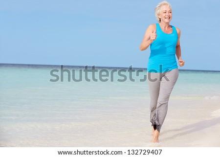 Senior Woman Running On Beautiful Beach - stock photo
