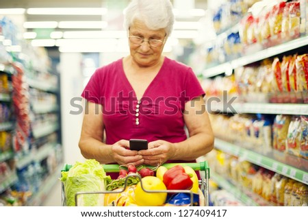 Senior woman send a text on mobile phone at supermarket - stock photo