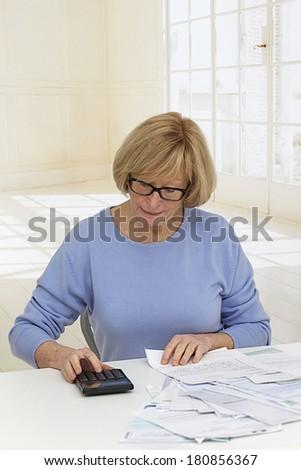 senior woman seriously doing home finances  - stock photo