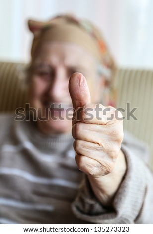 senior woman showing okay hand sign (gesture) and smiling for you - stock photo