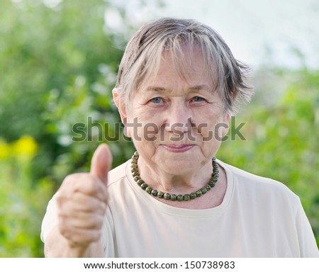 Senior woman showing thumbs up gesture outdoors  in summer. Selective focus - stock photo