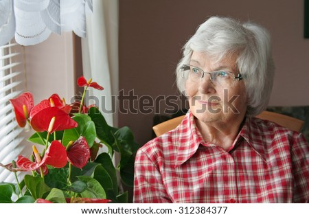 Senior woman sitting and looking out the window - stock photo