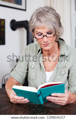 Senior woman sitting at a table reading a book with reading glasses is totally immersed in the story - stock photo