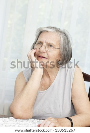 Senior woman sitting at the table with hand on her chin and looking away. - stock photo