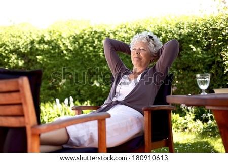 Senior woman sitting on a chair and taking a nap in backyard. Elder woman sleeping in backyard garden - stock photo