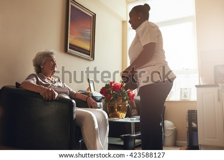 Senior woman sitting on a chair at home with female caregiver standing by. Female nurse visiting senior patient for checking blood pressure. - stock photo