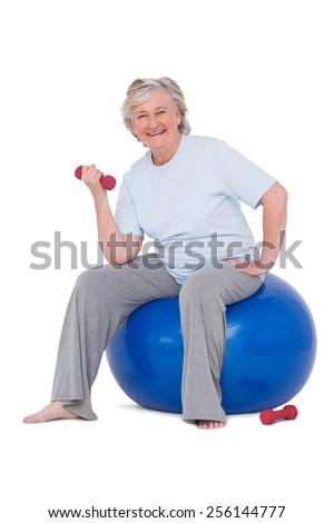Senior woman sitting on exercise ball on white background - stock photo
