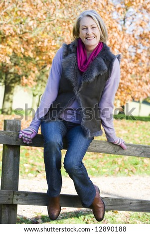 Senior woman sitting on fence with autumn trees in background - stock photo