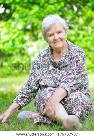 Senior woman sitting on grass in park. MANY OTHER PHOTOS FROM THIS SERIES IN MY PORTFOLIO. - stock photo