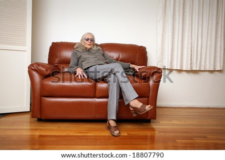 Senior woman sitting on leather sofa at home - stock photo