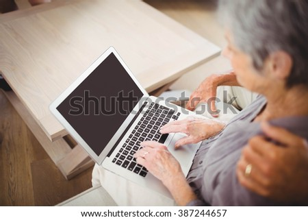 Senior woman sitting on sofa and using laptop in living room - stock photo