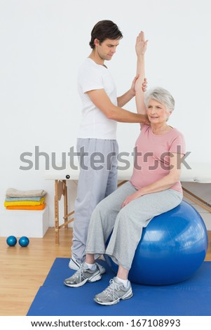 Senior woman sitting on yoga ball while working with a physical therapist - stock photo