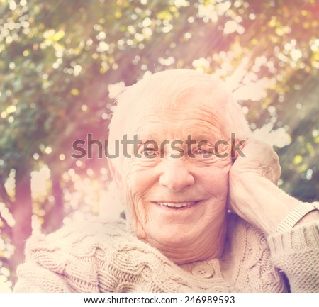 Senior woman sitting outdoors with a big happy smile  - stock photo