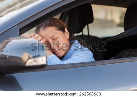 Senior woman sleeping in  black car.  - stock photo