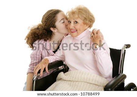 Senior woman smiles as she gets a kiss from her granddaughter.  Isolated on white. - stock photo