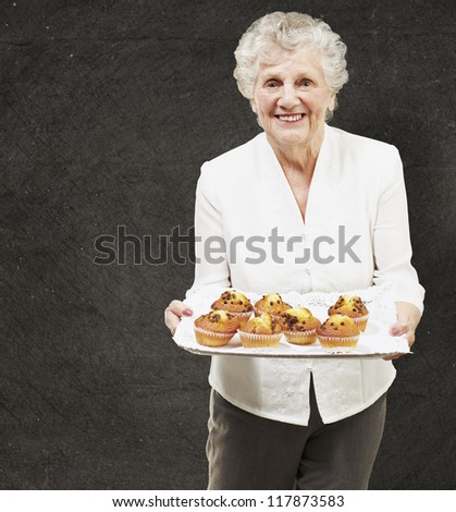 senior woman smiling and holding a tray with muffins against a grunge wall - stock photo