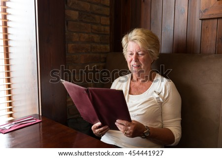 Senior woman smiling and reading a restaurant menu ready to order food - stock photo