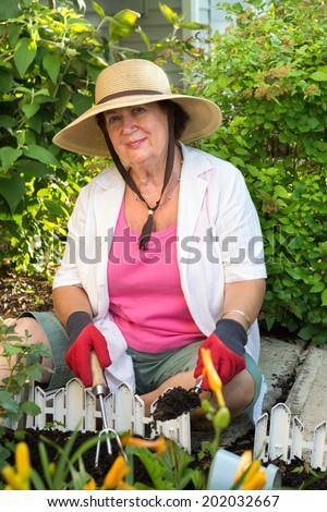 Senior woman smiling at camera wearing straw hat, casual clothes and gardening gloves while planting ornamental flowers in the garden, in a warm summer day - stock photo