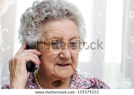 Senior woman speaking on mobile phone sitting in chair  - stock photo